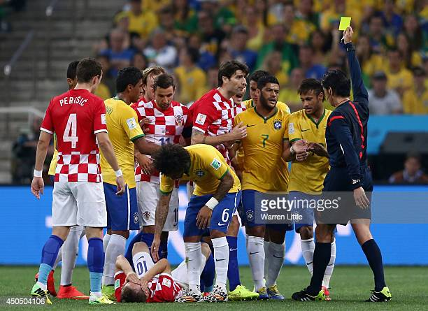 Neymar of Brazil is shown a yellow card by referee Yuichi Nishimura as Luka Modric of Croatia lies on the field during the 2014 FIFA World Cup Brazil...