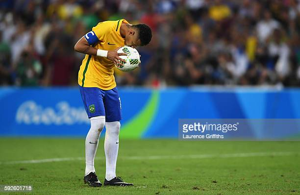 Neymar of Brazil kisses the ball as he prepares to take the winning penalty in the penalty shoot out during the Men's Football Final between Brazil...