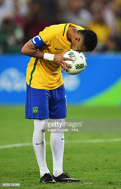 Neymar of Brazil kisses the ball before taking the winning penalty at the Olympic Men's Final Football match between Brazil and Germany at Maracana...
