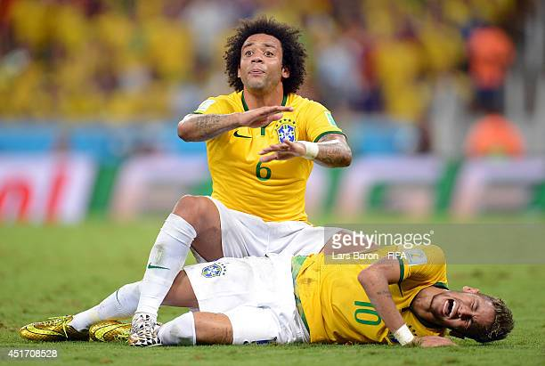 Neymar of Brazil lies injured while Marcelo of Brazil appeals during the 2014 FIFA World Cup Brazil Quarter Final match between Brazil and Colombia...