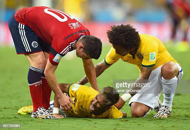 Neymar of Brazil lies on the field after a challenge as teammate Marcelo and James Rodriguez of Colombia look on during the 2014 FIFA World Cup...