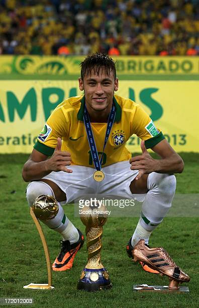 Neymar of Brazil poses with the trophy and his adidas Golden Ball and Bronze boot awards at the end of the FIFA Confederations Cup Brazil 2013 Final...