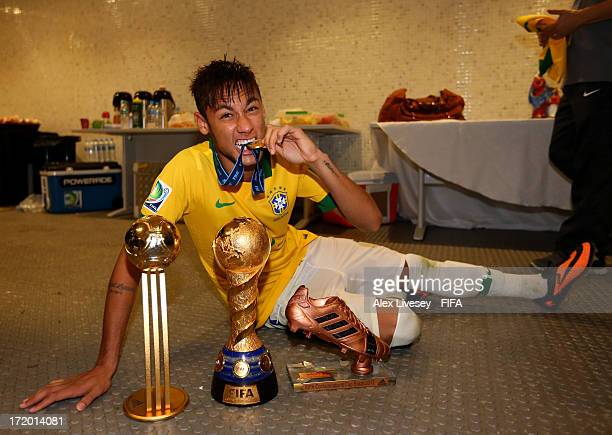 Neymar of Brazil poses with the trophy and his adidas Golden Ball and Bronze boot awards in the dressing room at the end of the FIFA Confederations...