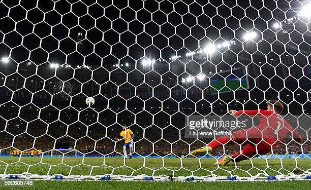 Neymar of Brazil scores his penalty in the shoot out during the Men's Football Final between Brazil and Germany at the Maracana Stadium on Day 15 of...