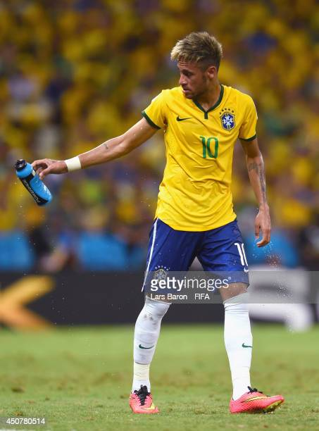 Neymar of Brazil throws a bottle after cooling down with water during the 2014 FIFA World Cup Brazil Group A match between Brazil and Mexico at...