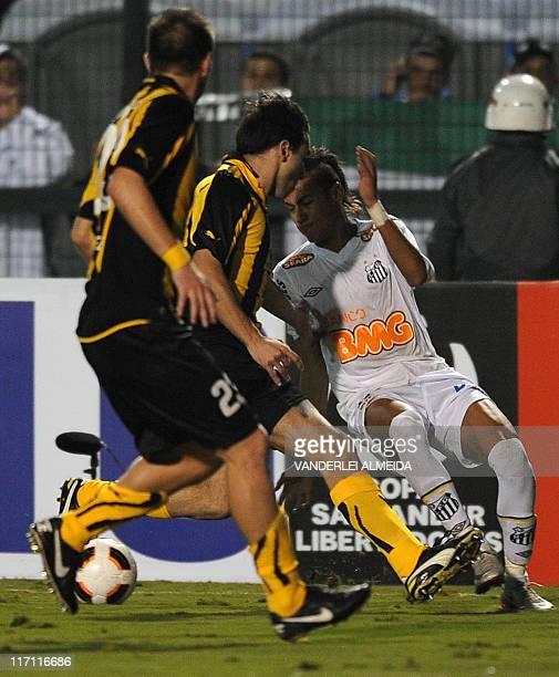 Neymar of Brazil's Santos vies for the ball with Carlos Valdez and Alejandro Gonzalez of Uruguay's Penarol during their Copa Libertadores final...
