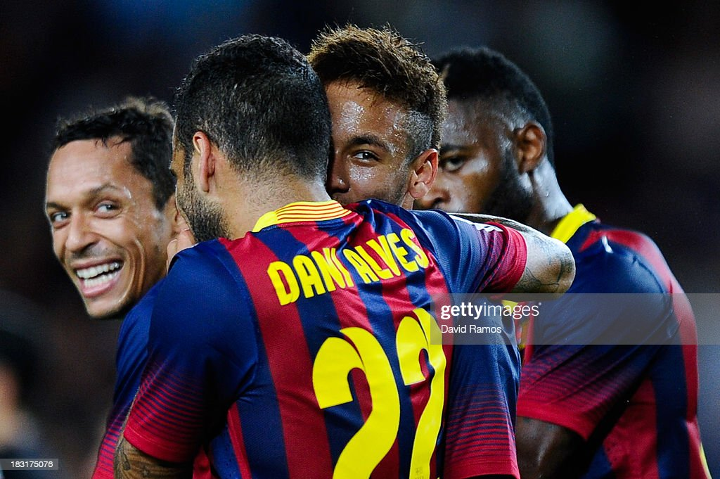 Neymar (C) of FC Barcelona celebrates with his team-mate Dani Alves after scoring his team's fourth goal during the La Liga match between FC Barcelona and Real Valladolid CF at Camp Nou on October 5, 2013 in Barcelona, Spain.