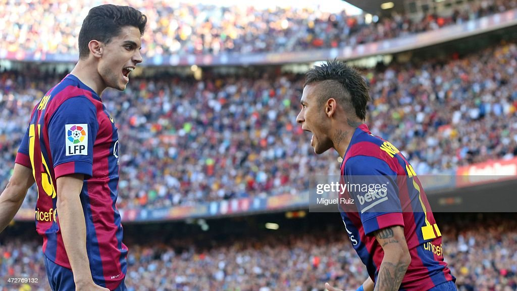 Neymar (R) of FC Barcelona celebrates with his team-mate Marc Bartra as he scored the first goal during the La Liga match between FC Barcelona and Real Sociedad de Futbol at Camp Nou on May 9, 2015 in Barcelona, Spain.