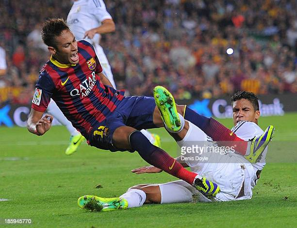 Neymar of FC Barcelona is brought down in a tackle by Raphael Varane of Real Madrid CF during the La Liga match between FC Barcelona and Real Madrid...