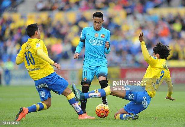 Neymar of FC Barcelona is tackled by Mauricio Lemos and Sergio Araujo of UD Las Palmas during the La Liga match between UD Las Palmas and FC...