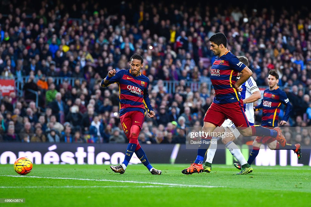 Neymar (L) of FC Barcelona scores his team's third goal during the La Liga match between FC Barcelona and Real Sociedad de Futbol at Camp Nou on November 28, 2015 in Barcelona, Spain.