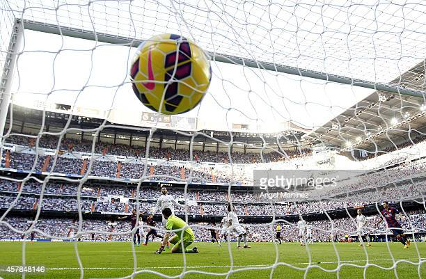 Neymar of FC Barcelona scores the opening goal past Iker Casillas of Real Madrid during the La Liga match between Real Madrid CF and FC Barcelona at...