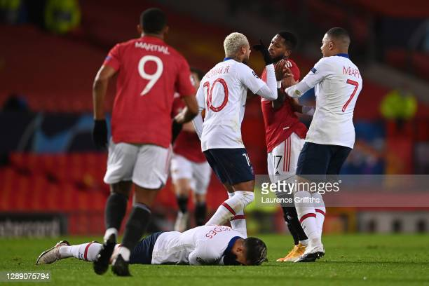 Neymar of Paris Saint Germain and Fred of Manchester United clash as Leandro Paredes of Paris Saint Germain lies on the floor during the UEFA...