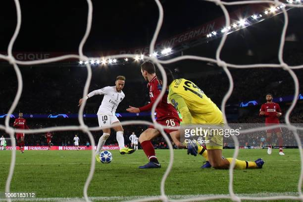 Neymar of Paris SaintGermain scores his sides second goal past Alisson of Liverpool during the UEFA Champions League Group C match between Paris...