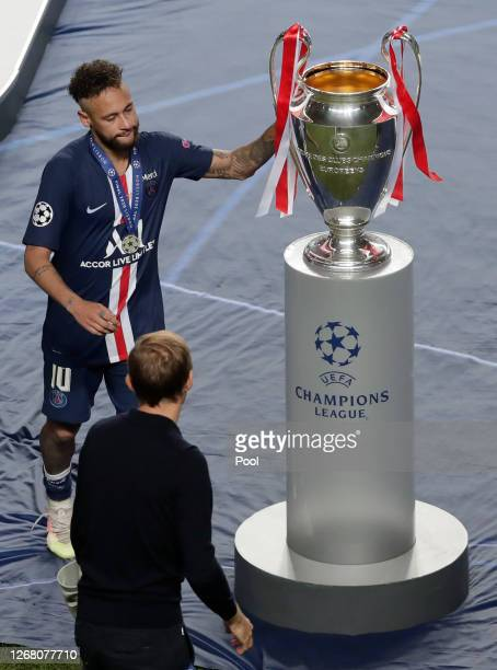 Neymar of Paris SaintGermain touches the UEFA Champions League Trophy as he looks dejected with his runners up medal following his team's defeat in...