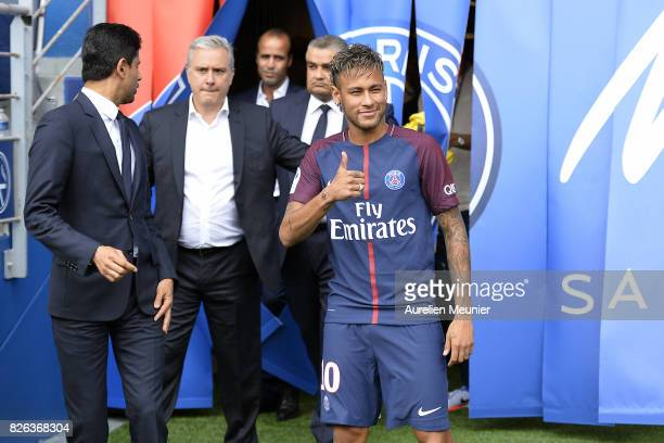Neymar salutes the press as he arrives to pose with his new jersey after a press conference with Paris SaintGermain President Nasser AlKhelaifi on...