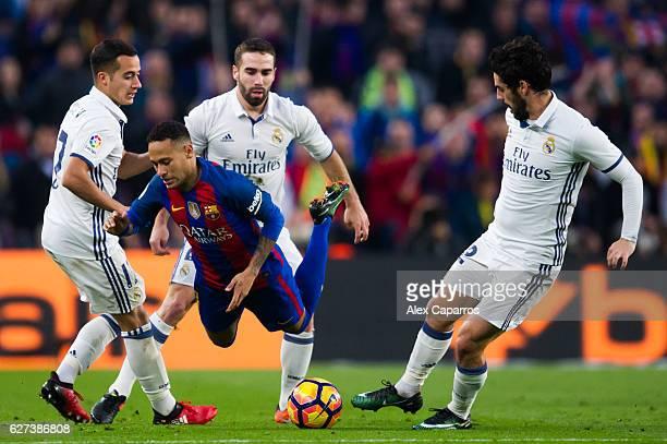 Neymar Santos Jr of FC Barcelona falls between Lucas Vazquez Daniel Carvajal and Francisco Alarcon 'Isco' during the La Liga match between FC...