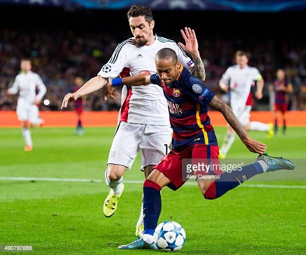 Neymar Santos Jr of FC Barcelona kicks the ball under a challenge of Roberto Hilbert of Bayer 04 Leverkusen during the UEFA Champions League Group E...