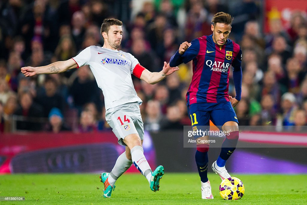 Neymar Santos Jr of FC Barcelona passes the ball next to Gabriel 'Gabi' Fernandez of Club Atletico de Madrid during the La Liga match between FC Barcelona and Club Atletico de Madrid at Camp Nou on January 11, 2015 in Barcelona, Spain.