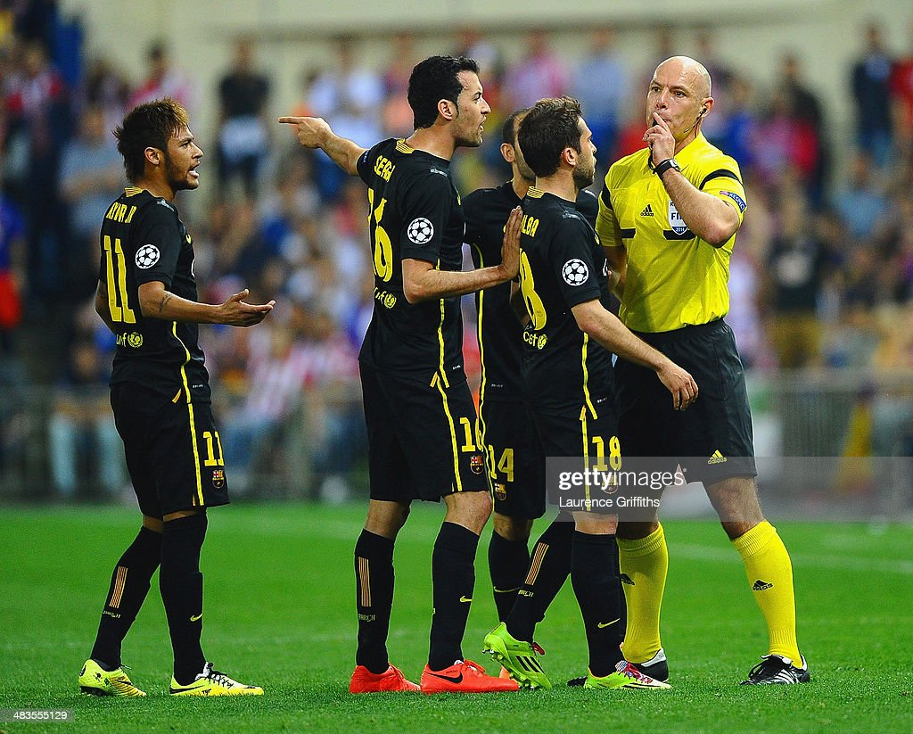Neymar, Sergio Busquets and Jordi Alba of Barcelona surround referee Howard Webb during the UEFA Champions League Quarter Final second leg match between Club Atletico de Madrid and FC Barcelona at Vicente Calderon Stadium on April 9, 2014 in Madrid, Spain.