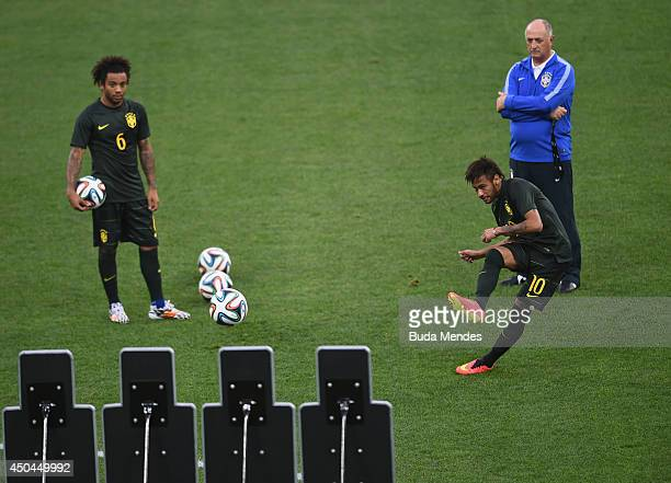 Neymar shoots as Marcelo and manager Luiz Felipe Scolari of Brazil look on during a Brazil training session ahead of the 2014 FIFA World Cup Brazil...