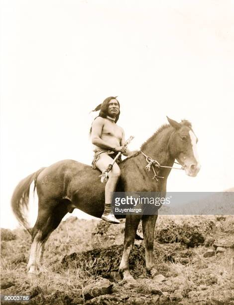 Nez Percé man wearing loin cloth and moccasins on horseback