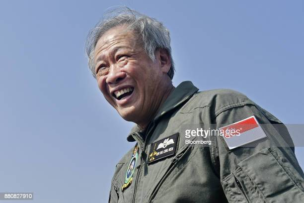 Ng Eng Hen Singapore's defense minister center left reacts while speaking to members of the media after his flight in an Indian Air Force Tejas...
