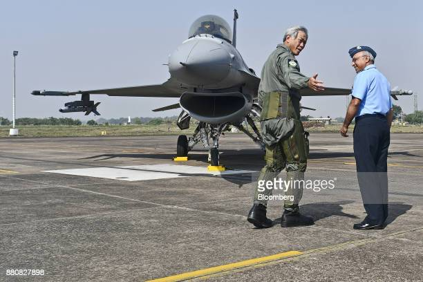 Ng Eng Hen Singapore's defense minister center left speaks to members of the media after his flight in an Indian Air Force Tejas fighter jet at the...