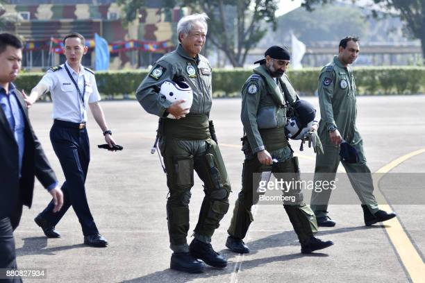 Ng Eng Hen Singapore's defense minister center left walks to an Indian Air Force Tejas fighter jet prior to his flight at the Kalaikunda Air Force...