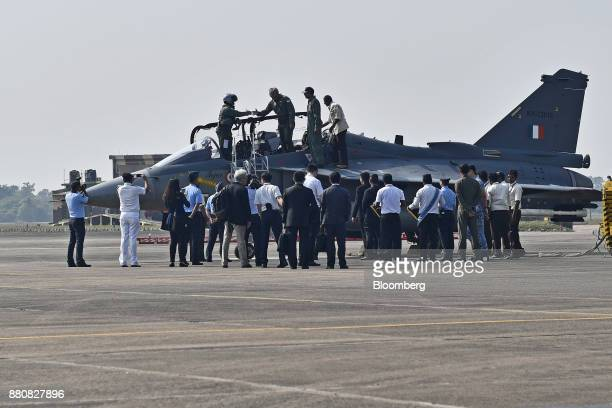 Ng Eng Hen Singapore's defense minister center shakes hands with the pilot after his flight in an Indian Air Force Tejas fighter jet at the...