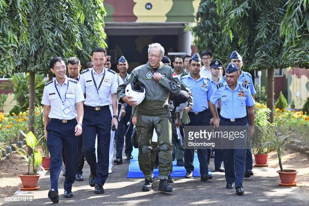 Ng Eng Hen Singapore's defense minister center walks to an Indian Air Force Tejas fighter jet prior to his flight at the Kalaikunda Air Force Sation...