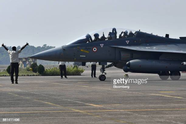 Ng Eng Hen Singapore's defense minister right salutes while sitting in an Indian Air Force Tejas fighter jet at the Kalaikunda Air Force Station West...