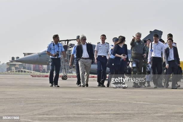 Ng Eng Hen Singapore's defense minister third from right walks from an Indian Air Force Tejas fighter jet after his flight at the Kalaikunda Air...