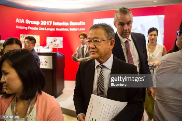 Ng Keng Hooi chief executive officer and president of AIA Group Ltd center leaves following a news conference in Hong Kong China on Friday July 28...