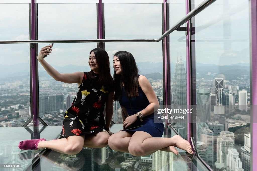 TOPSHOT - Ng Sin Nee (L) and Lee Shin May (R) from Malaysia take pictures with the panoramic view of the city from the Sky Box at KL Tower, the world's seventh tallest telecommunications tower, in Kuala Lumpur on May 24, 2016. Officially opened on May 20, the Sky Box has been the latest attraction for tourists arriving to the Malaysian capital. It stands 300 metres above ground and can fit six people at any one time, and offers spectacular views of the Kuala Lumpur skyline, including the iconic Petronas Twin Towers. / AFP / MOHD