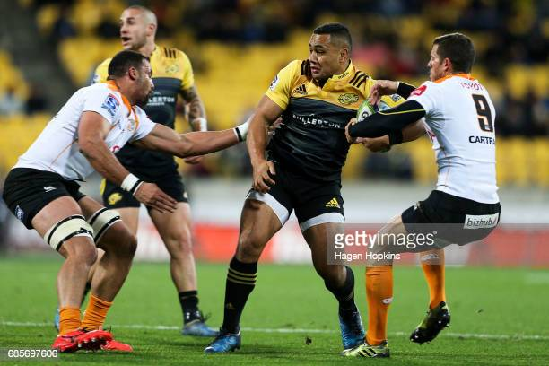 Ngani Laumape of the Hurricanes is tackled by Shaun Venter and Uzair Cassiem of the Cheetahs during the round 13 Super Rugby match between the...