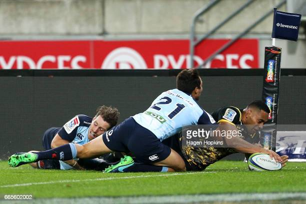 Ngani Laumape of the Hurricanes scores a try in the tackle of Bernard Foley and Nick Phipps of the Waratahs during the round seven Super Rugby match...