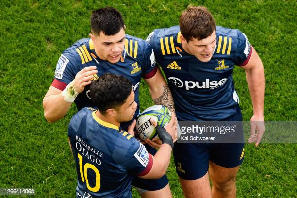 Ngatungane Punivai of the Highlanders is congratulated by Josh Ioane of the Highlanders and Michael Collins of the Highlanders after scoring a try...