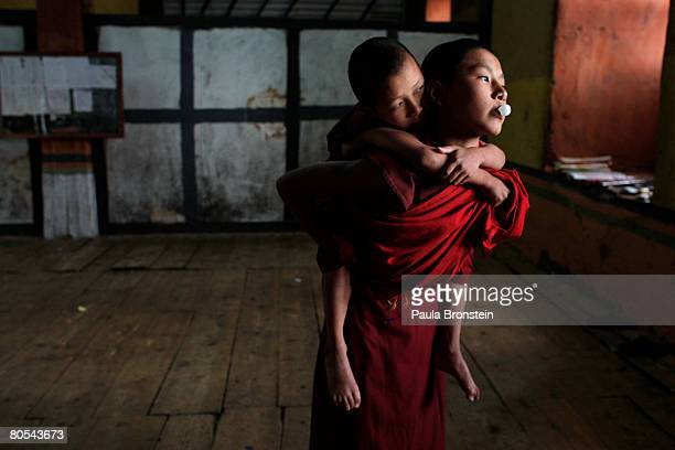 Ngedup holds Sonam who is one of the youngest monks at the Paro Dzong April 2 2008 in Paro Bhutan A Dzong holds both the administrative governing...