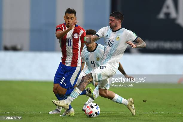 Ángel Romero of Paraguay competes for the ball with Rodrigo de Paul of Argentina during a match between Argentina and Paraguay as part of South...