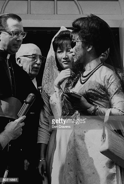 Ngo Dinh Le Thuy and her mother Ngo Dinh Nhu standing with a priest shortly after learning of revolt in Vietnam