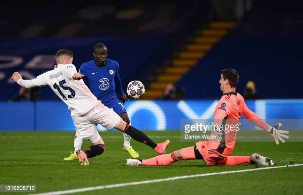 Ngolo Kante of Chelsea shoots under pressure from Thibaut Courtois and Federico Valverde of Real Madrid during the UEFA Champions League Semi Final...