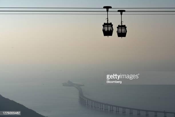 Ngong Ping cable cars travel past the Hong Kong-Zhuhai-Macau Bridge in Hong Kong, China, on Saturday, Oct. 3, 2020. Hong Kong's economy is showing...
