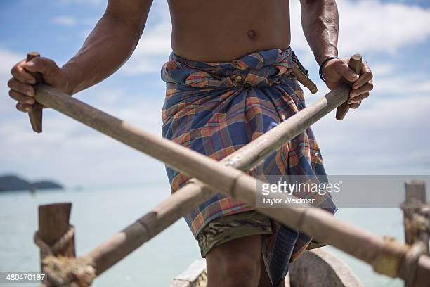 Nguy an indigenous Moken man rows a sampan out from his village in the Ko Surin National Park Thailand Often called sea nomads or sea gypsies the...