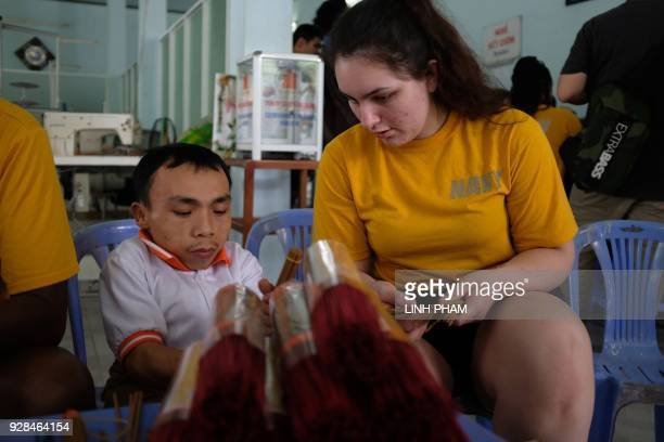 Nguyen Ngoc Phuong who suffers the affects of Agent Orange sits beside a US Navy sailor during a visit by the crew of USS Carl Vinson in Danang on...