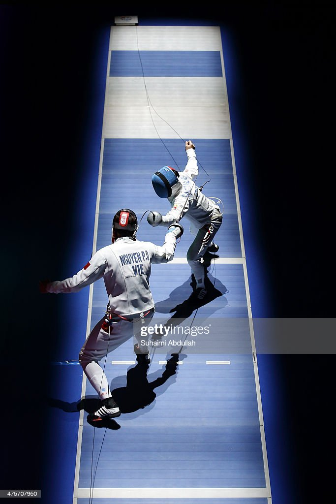 Nguyen Phuoc Den of Vietnam (front) competes against Lee Mun Hou Samson of Singapore during the men's individual epee quarterfinals match at OCBC Arena Hall during the 2015 SEA Games on June 3, 2015 in Singapore.