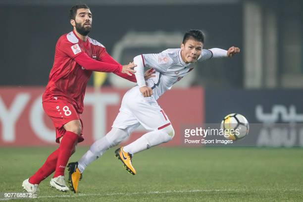 Nguyen Quang Hai of Vietnam fights for the ball with Mouhamad Anez of Syria during the AFC U23 Championship China 2018 Group D match between Syria...