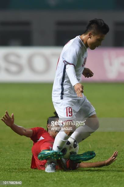 Nguyen Quang Hai of Vietnam vies for the ball with Hemant Thapa Magar of Nepal in the Group D match between Nepal and Vietnam of the 2018 Asian Games...