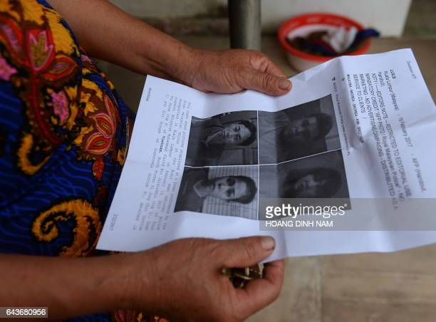 CORRECTION Nguyen Thi Vy stepmother of Doan Thi Huong a suspect involved in the assassination of Kim JongUn's halfbrother looks at handouts and...