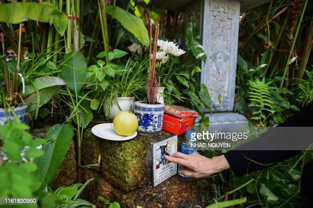 Nguyen Thi Xuan Trang is touches the plague of her dog while praying at Te Dong Vat Nga pagoda which means all lives are equal a cemetery for pets in...